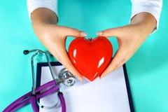 Docteur féminin avec le coeur de fixation de stéthoscope Docteur et patient s'asseyant à l'arrière-plan Image libre de droits