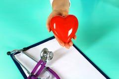 Docteur féminin avec le coeur de fixation de stéthoscope Docteur et patient s'asseyant à l'arrière-plan Photographie stock libre de droits