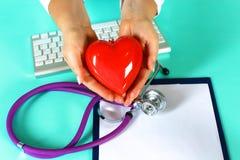 Docteur féminin avec le coeur de fixation de stéthoscope Docteur et patient s'asseyant à l'arrière-plan Photographie stock
