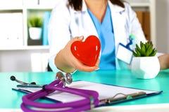 Docteur féminin avec le coeur de fixation de stéthoscope Docteur et patient s'asseyant à l'arrière-plan Images stock