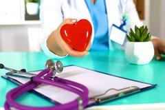 Docteur féminin avec le coeur de fixation de stéthoscope Docteur et patient s'asseyant à l'arrière-plan Photos stock