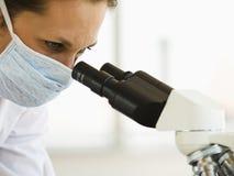 Docteur féminin avec le microscope Images stock