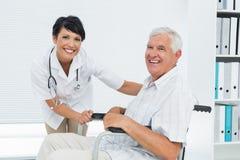 Docteur féminin avec le patient supérieur dans le fauteuil roulant Images stock