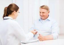 Docteur féminin avec le vieil homme donnant la prescription images stock