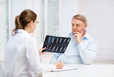 Docteur féminin avec le vieil homme regardant le rayon X Photos stock