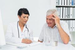 Docteur féminin avec les rapports patients masculins de lecture photo stock