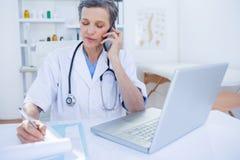 Docteur féminin ayant un appel téléphonique Photo stock
