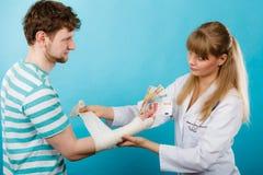 Docteur féminin bandant la main masculine Photographie stock