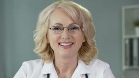 Docteur féminin blond mûr dans l'uniforme souriant dans l'appareil-photo, clinique de soins de santé banque de vidéos