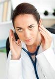 Docteur féminin confiant retenant un stéthoscope photographie stock
