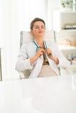 Docteur féminin décontracté s'asseyant à un bureau dans le bureau photos libres de droits