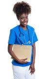 Docteur féminin d'afro-américain avec les cheveux bouclés et le dossier images stock
