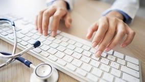 Docteur féminin dactylographiant sur l'ordinateur image stock