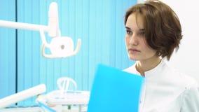 Docteur féminin dans les notes patientes de lecture d'armoire de dentiste devant le matériel médical, concept de soins de santé D banque de vidéos