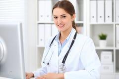 Docteur féminin de jeune brune s'asseyant à la table et travaillant au bureau d'hôpital Photo libre de droits