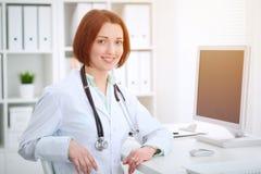 Docteur féminin de jeune brune s'asseyant à la table et travaillant avec l'ordinateur au bureau d'hôpital photos libres de droits