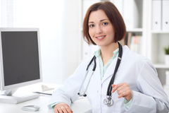 Docteur féminin de jeune brune s'asseyant à un bureau et travaillant sur l'ordinateur au bureau d'hôpital Images libres de droits