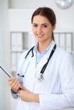 Docteur féminin de jeune brune se tenant avec le presse-papiers et souriant à l'hôpital Médecin prêt à examiner le patient photo stock