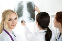 Docteur féminin de médecine avec deux collègues regardant le pict de rayon X photo libre de droits