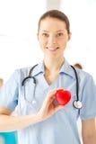 Docteur féminin de sourire avec le coeur un stéthoscope Photographie stock