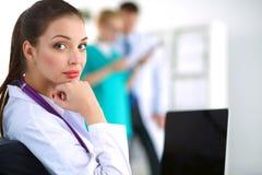 Docteur féminin de sourire de beaux jeunes s'asseyant au bureau image libre de droits