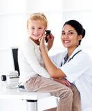 Docteur féminin de sourire contrôlant les oreilles de son patient Images libres de droits