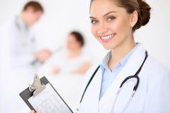 Docteur féminin de sourire gai sur le fond avec le docteur et son patient dans le lit Haut niveau et qualité de Images stock