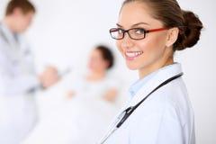 Docteur féminin de sourire gai sur le fond avec le docteur et son patient dans le lit Haut niveau et qualité de Photos stock