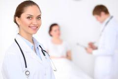 Docteur féminin de sourire gai sur le fond avec le docteur et son patient dans le lit Haut niveau et qualité de Photographie stock libre de droits
