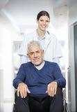 Docteur féminin de sourire Pushing Senior Patient dans le fauteuil roulant Photographie stock