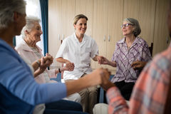 Docteur féminin de sourire tenant des mains avec des aînés tout en se reposant sur des chaises Photos libres de droits
