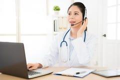 Docteur féminin de sourire tenant dessus l'écouteur images libres de droits