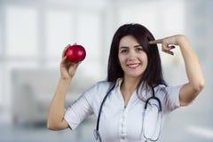 Docteur féminin de sourire tenant la pomme rouge images libres de droits
