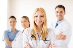Docteur féminin devant le groupe médical Image stock