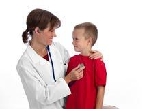 Docteur féminin donnant à un garçon une visite médicale Photographie stock libre de droits