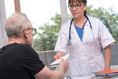 Docteur féminin donnant la prescription à son patient Image stock
