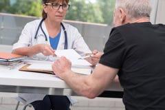 Docteur féminin donnant la prescription à son patient Photo stock
