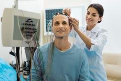 Docteur féminin enlevant des électrodes de la tête de patients Photographie stock libre de droits