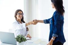 Docteur féminin et son patient se serrant la main dans la consultation Photos libres de droits