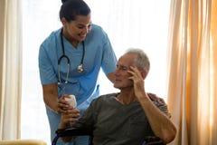 Docteur féminin examinant l'homme supérieur s'asseyant sur le fauteuil roulant Images libres de droits