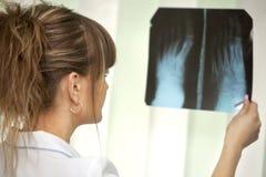 Docteur féminin examinant un rayon X Images libres de droits