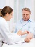 Docteur féminin faisant l'injection au vieil homme Photo stock