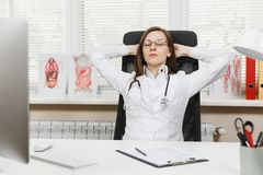 Docteur féminin fatigué de jeunes s'asseyant et dormant au bureau dans le bureau léger dans l'hôpital Femme dans la robe médicale photo libre de droits