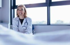Docteur féminin heureux s'asseyant dans la chambre d'hôpital photo libre de droits