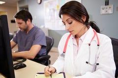 Docteur féminin With Male Nurse travaillant à la station d'infirmières Photo stock