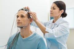 Docteur féminin mettant des électrodes sur la tête de patients Photos libres de droits