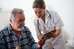 Docteur féminin montrant le comprimé numérique à l'homme supérieur photos libres de droits