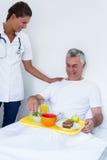 Docteur féminin parlant à l'homme supérieur tout en prenant le petit déjeuner photo libre de droits