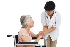 Docteur féminin parlant à un patient supérieur dans le fauteuil roulant Images stock
