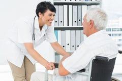 Docteur féminin parlant à un patient supérieur dans le fauteuil roulant Photographie stock